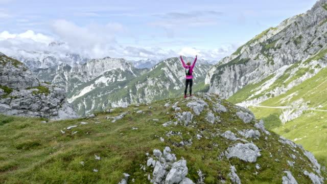 공중 여자 써니 밸리 상공에 높은 발생 하는 그녀의 손으로 산 위에 서 서 - mountain top 스톡 비디오 및 b-롤 화면