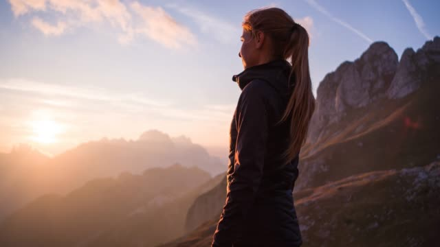 woman standing on top of mountain, enjoying breathtaking view at sunset - trekking video stock e b–roll
