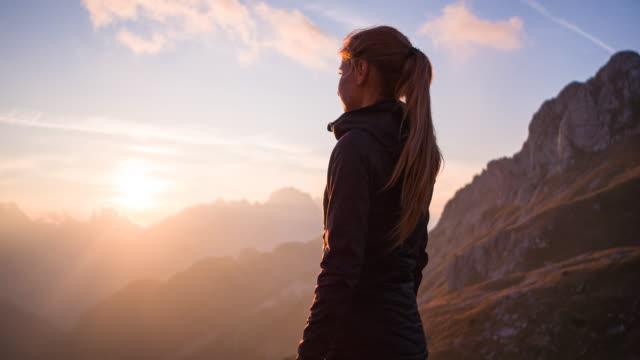 vídeos y material grabado en eventos de stock de mujer de pie en la cima de la montaña, disfrutando de una vista impresionante al atardecer - esperar