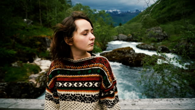 Woman standing on Wooden Bridge on the mountain river in Norway Young Caucasian woman standing on Wooden Bridge on the mountain river in Norway scandinavia stock videos & royalty-free footage