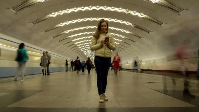 kvinna står fortfarande i tunnelbanestation och med hjälp av mobiltelefon. skara människor och passerande tåg - stationär bildbanksvideor och videomaterial från bakom kulisserna
