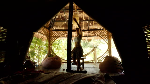 Woman standing up and going out of Tent in a tropical forest in El Nido, Philippines