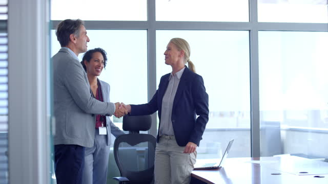 SLO MO Woman standing up to greet a man walking into the meeting room Slow motion wide shot of a woman standing up and shaking hands with a man walking into the conference room. Shot in Slovenia. businesswear stock videos & royalty-free footage