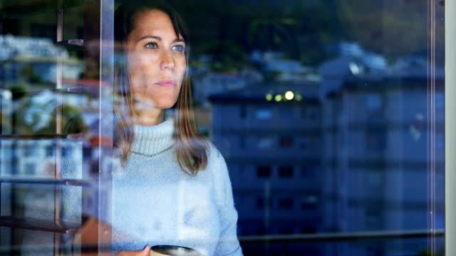 vidéos et rushes de femme debout avec une tasse de café près de la fenêtre 4k - 40 44 ans