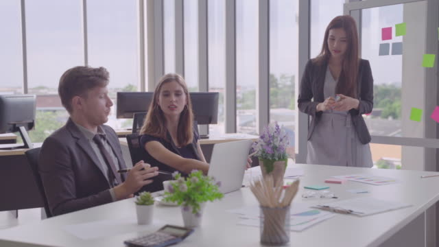 woman standing with presentation boards.ethnically diverse business and are talking to or meeting with business partners about a star up in the meeting.concepts, brainstorming conferences and business development of partners - debate стоковые видео и кадры b-roll