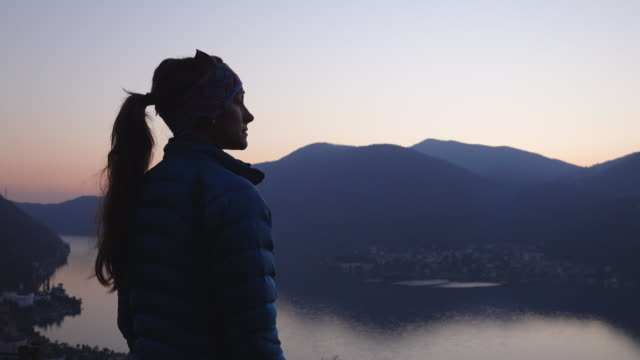 Woman stands after sunset at viewpoint looking out at view of lake and mountains Using technology in nature at dusk 30 39 years stock videos & royalty-free footage
