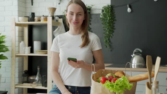 女性は生鮮食品でいっぱいの紙袋の近くの台所に立ち、スマートフォンアプリを使ってスーパーマーケットに届ける - クレジット決済点の映像素材/bロール