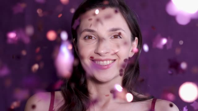 woman stands in the Studio on a purple background with confetti