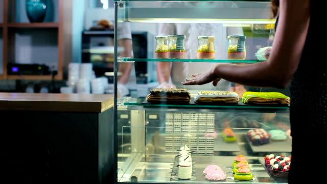 Une femme se tient près d'un écran de desserts. - Vidéo