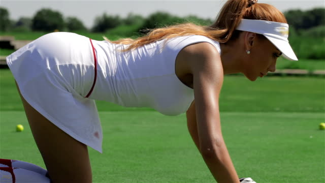 Woman stands on all fours in front of the hole at the golf video