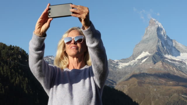 stockvideo's en b-roll-footage met vrouw staat op heuvel met slimme telefoon, matterhorn verre - matterhorn