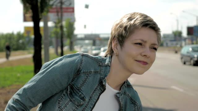 Woman stands on roadside of city street traffic video