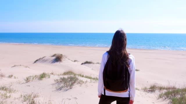 woman stands on sea sand beach among dunes and looks at sea vacation back view. - brązowe włosy filmów i materiałów b-roll