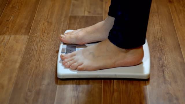 stockvideo's en b-roll-footage met een vrouw staat op de weegschaal en leert haar gewicht, close-up - vrouwelijkheid