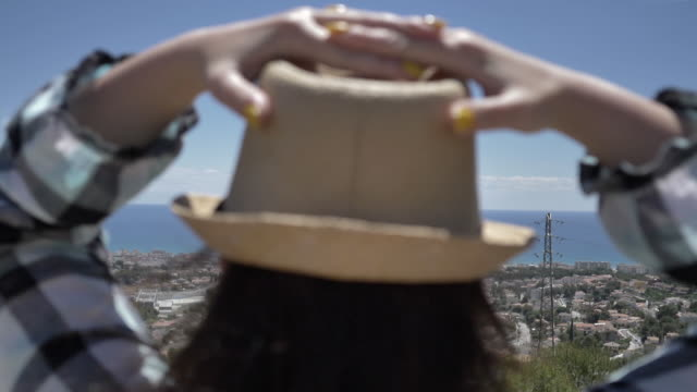 woman stands on top and looks at the city and the sea, holding her hat, windy video