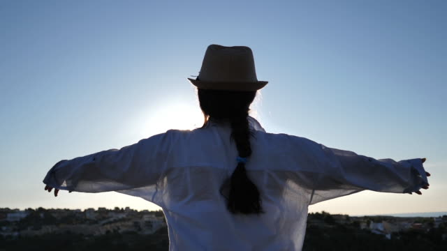 woman stands on top and looks, raising her hands to the sun at dawn video