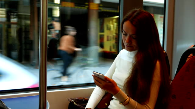 Woman stare at smartphone, travel in tram at shopping street video