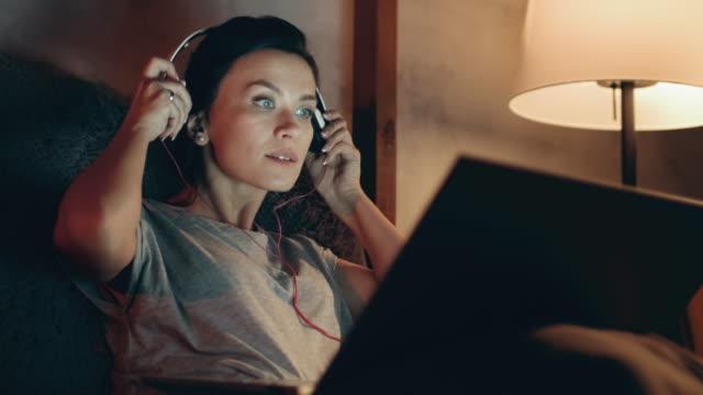 Woman starts watching movie on laptop. Brunette listening music on headphones.