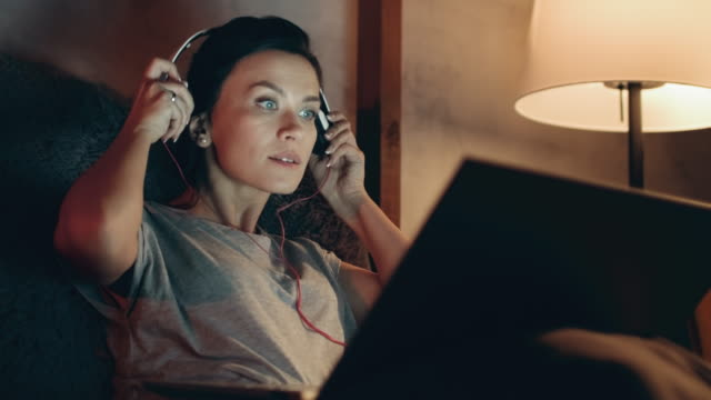 Woman starts watching movie on laptop. Brunette listening music on headphones. Portrait of relaxed woman watching movie on laptop at evening home. Closeup smiling girl relaxing with notebook on couch. Attractive brunette listening music on headphones at night in room. contented emotion stock videos & royalty-free footage