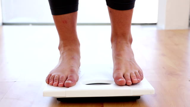 Woman stepping on scales video