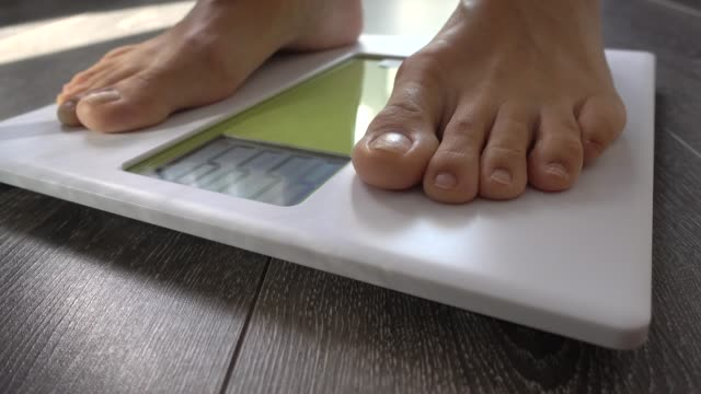 VIDEO 4K, woman stepping on weighting scale, at home, on wooden floor