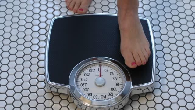 woman stepping onto scale - вес стоковые видео и кадры b-roll