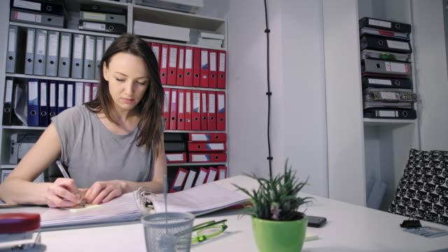 vídeos de stock e filmes b-roll de woman sticking adhesive notes - dossier