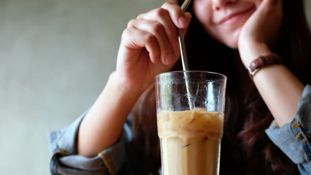 a woman stirring iced coffee with stainless steel straw - paglia video stock e b–roll
