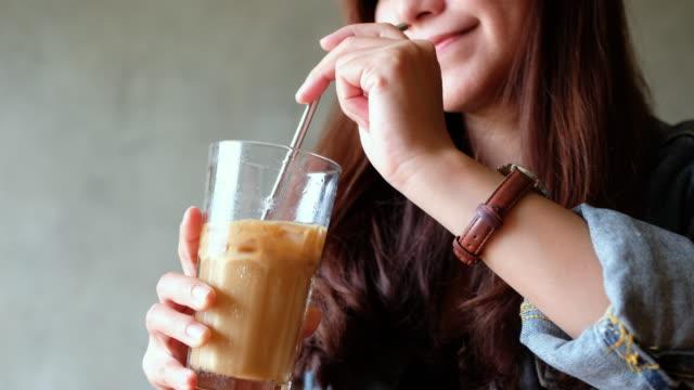 ステンレススチールストローでアイスコーヒーをかき混ぜる女性 - environmentalism点の映像素材/bロール