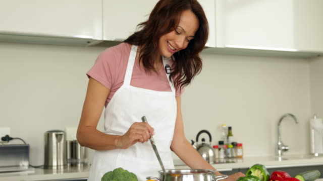 Woman stirring saucepan with lots of vegetables on counter video