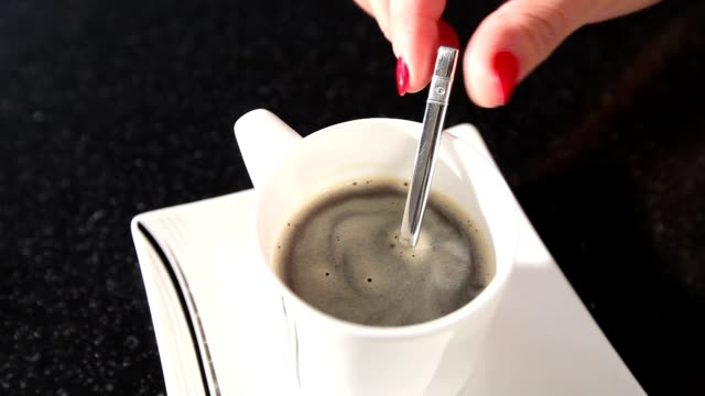 A woman stirs a coffee with a spoon, A girl stirs sugar in a coffee spoon, close-up video