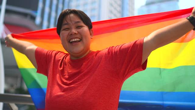 vídeos de stock, filmes e b-roll de uma mulher ficou sorrindo, levantando uma bandeira do arco-íris. é um símbolo do orgulho lésbico, gay, bissexual, transgênero e gay (lgbtq) e movimentos sociais lgbtq. - lgbt