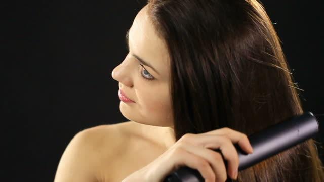 Woman straightening her hair video