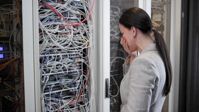 woman stressing about the cable mess in the server room and walking away - rabbia emozione negativa video stock e b–roll
