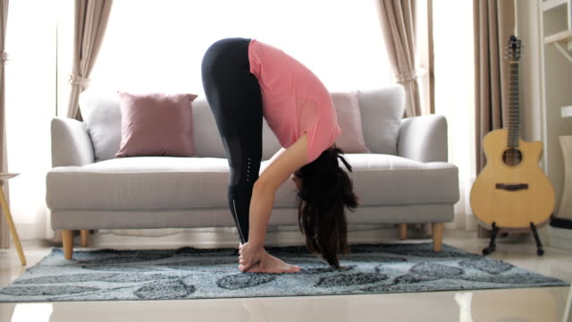 woman stretching and exercise at home during coronavirus covid-19 quarantine - inarcare la schiena video stock e b–roll