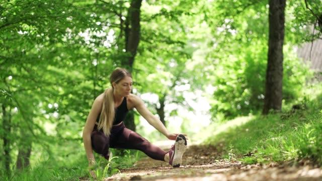 woman stretching before training - ludzka kończyna filmów i materiałów b-roll