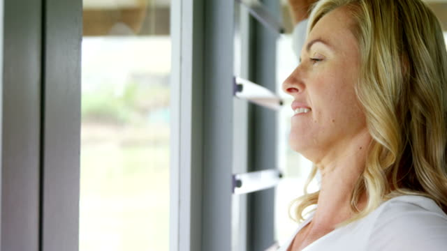 Woman stretching her arms near the window 4k video