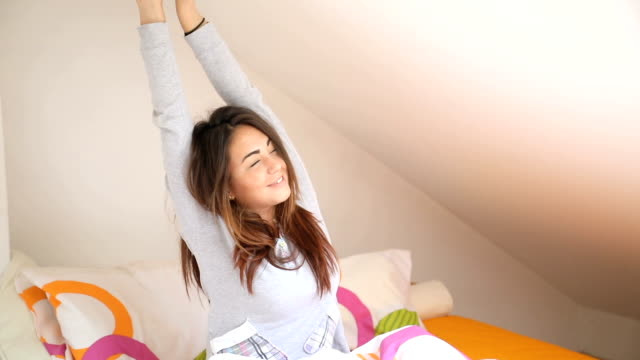 vídeos de stock e filmes b-roll de woman stretching in bed after wake up - acordar