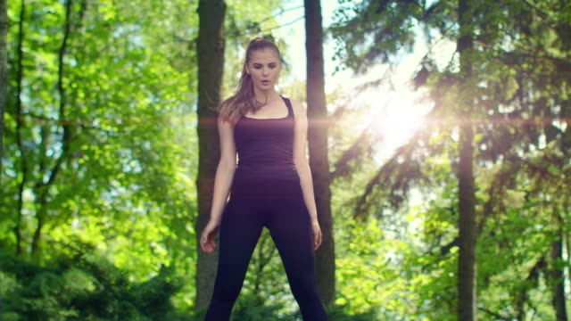 Woman stretching in park at morning. Woman exercising outdoor video