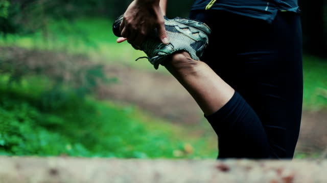 Woman stretching in the forest after running video