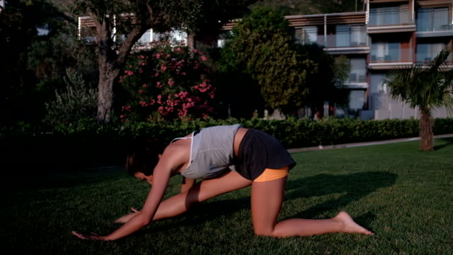 Woman stretching leg muscles on ground in evening outdoors video
