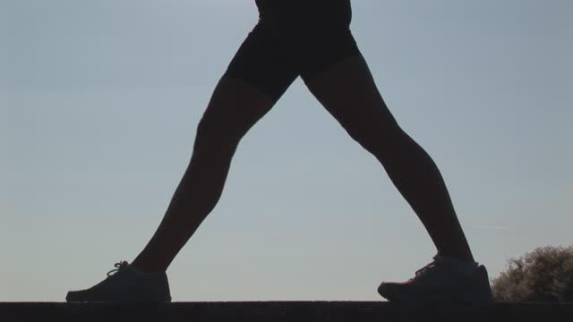 stockvideo's en b-roll-footage met woman stretching - lunge close - handen op de heupen