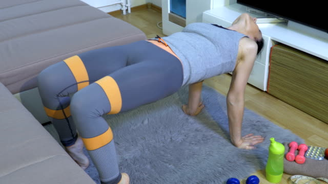 Woman stretching on floor and checking weight on scale - vídeo