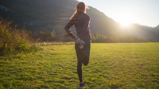 Woman stretching outdoors in fresh air in nature, doing a standing quadriceps stretch
