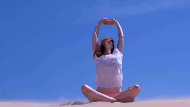 Woman stretching sits lotus pose sandy beach summer vacation hands up windy day. video