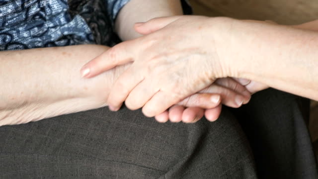 Woman strokes an old wrinkled woman's hand video
