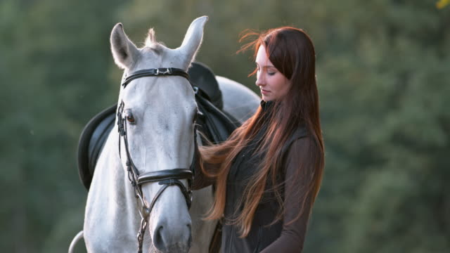 SLO MO Woman stroking her white horse in nature