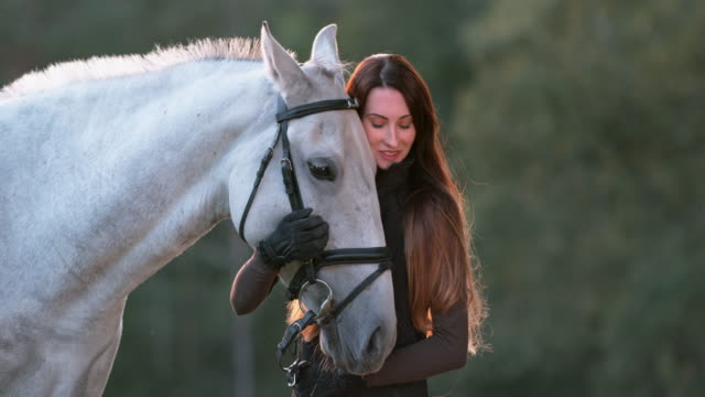 SLO MO Woman stroking white horse and talking to it