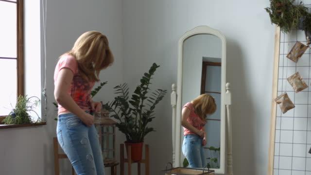 woman struggling trying to fit into tight jeans - dżinsy filmów i materiałów b-roll