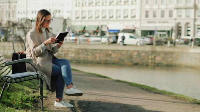 A woman studying outside on university campus A woman is sitting outdoors in the city on a sunny spring day. She is on campus, studying alone. scandinavia stock videos & royalty-free footage